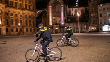 Police officers patrol a street in Amsterdam, Netherlands, where an emergency nighttime curfew has been introduced for the first time since World War II.