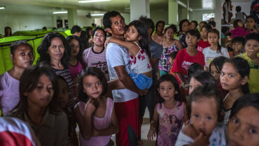 Evacuees queue to receive relief goods at an evacuation center during the onslaught of Typhoon Kammuri, in Batangas, Philippines.