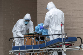 Medical personnel remove their protective gear after transporting bodies from the Wyckoff Heights Medical Centre in Brooklyn.