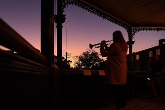 Bugler Sarah Brown, 23, plays The Last Post from the balcony of The Royal Hotel in Leichhardt on April 25, 2020.