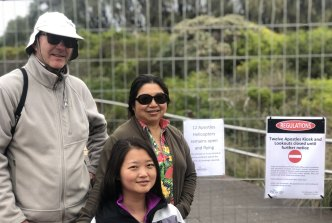 Andrew Dawson with wife Debbie Ng (rear) and sister-in-law Kate Zhong, at the fence preventing access to the Twelve Apostles viewing platforms on Sunday.