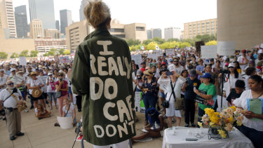 "Actress and activist Cheryl Allison wears a ""I Really DO Care, Don't U"" green jacket as she speaks during the Keep Families Together rally at Dallas City Hall  on Saturday."