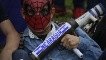An anti-government university student wearing a spider man mask holds a home made mortar during a protest outside the Jesuit-run Universidad Centroamericana, UCA, demanding the university's allocation of its share of six per cent of the national budget, in Managua, Nicaragua.