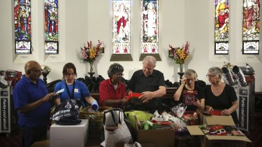 Reverend Bill Crews and volunteers of the Exodus Foundation sort through Christmas donations at their Ashfield parish prior to Chrismas Day.