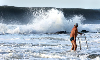 An ocean swimmer watches on as a wave rears up at Austinmer Beach on Saturday morning.
