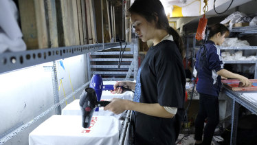 Staff at Thanh's Hanoi workshop drying just-printed T-shirts with hairdryers on Tuesday.