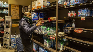 A man buys supplies of bottled water in Milan, Italy.