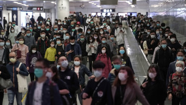 Commuters wear face masks as a precaution against the COVID-19 illness inside a subway station during rush hour in Hong Kong.