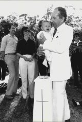 Ted Noffs of the Wayside Chapel performs a naming ceremony in a flared white suit in 1982.