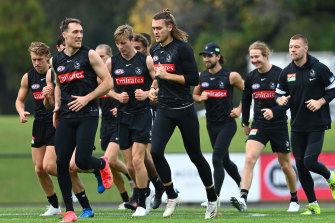 On the run: Collingwood players training this week.