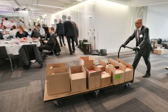 A Treasury and Finance staffer with a trolley load of budget papers.