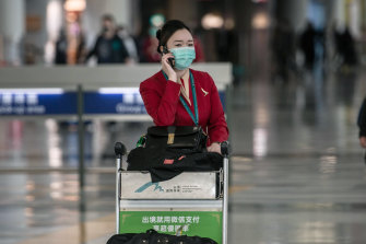 A Cathay Pacific employee pushes a luggage cart through Hong Kong International Airport.