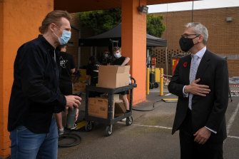 Masked men: Neeson, left, with Creative Industries minister Danny Pearson.