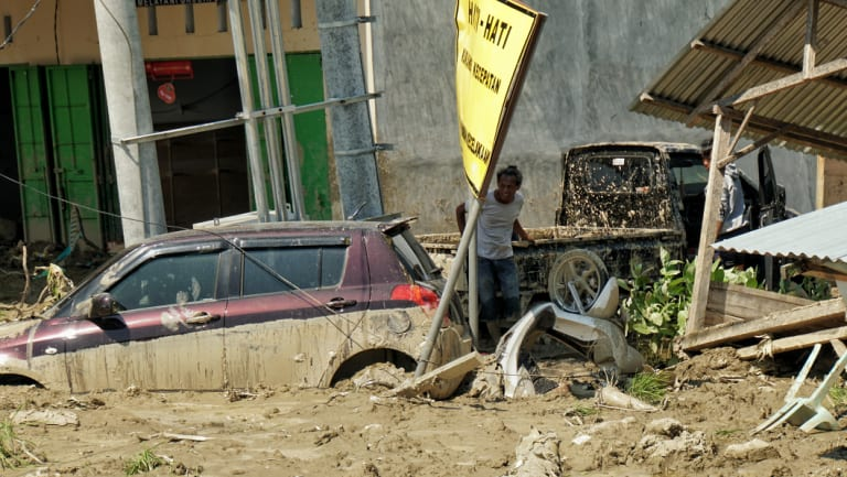 Two desperate locals searching  trapped and damaged cars to siphon the fuel off in Palu.