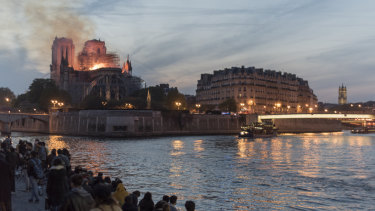 People watch as fire and smoke rise from a fire at Notre-Dame Cathedral in Paris, France.