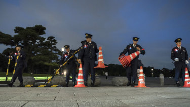 Police officers place traffic cones outside the Imperial Palace at night as Japan prepares for the enthronement of Emperor Naruhito, which takes place this week in Tokyo, Japan.