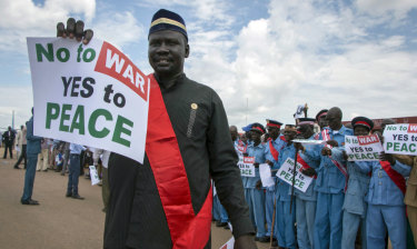 South Sudanese people hold signs as talks to end the five-year civil war were under way.