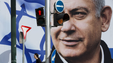 A woman walks by an election campaign billboard showing Israel's Prime Minister Benjamin Netanyahu, the Likud party leader, in Tel Aviv, Israel, on Thursday, March 28.