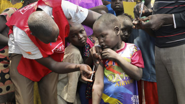 A community health worker vaccinates children against measles outside of Kuajok, South Sudan.