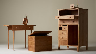 The chest of drawers has a candelabra, hand mirror, desk and coat rack.