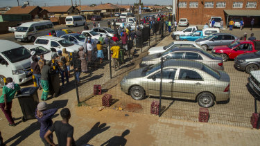 Customers queue to buy alcohol outside the Sam Liquor Store in Thokoza township, near Johannesburg.