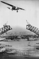 The Southern Cloud flies over an uncompleted Sydney Harbour Bridge.