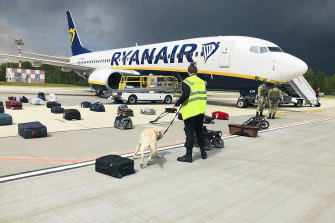 Belarusian security checks luggage on the grounded Ryanair flight in Minsk on Sunday.