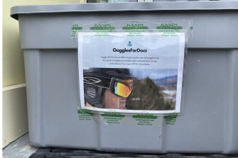 Skiers and snowboarders are asked to donate goggles for medical use outside a ski shop in Vermont.