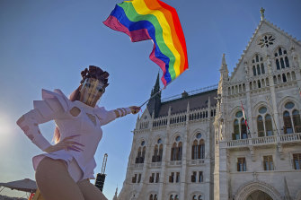 A drag queen waves a rainbow flag during a protest in front of the Hungarian Parliament building in Budapest.