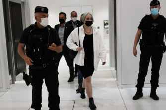 The teenager identified by her first name, Mila, leaves the courtroom in Paris. Thirteen others are charged with threatening her.