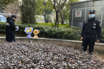 A security guard stands neaby as a man visiting the Wuhan Central Hospital leaves flowers in memory of whistleblower doctor Li Wenliang.