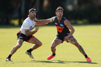 Tim Taranto holds off GWS assistant coach Mark McVeigh in a training drill.