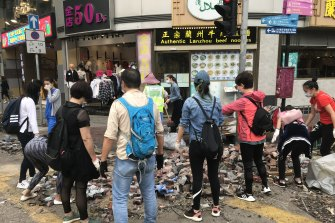 Hong Kong residents including May, 39, volunteer to clean up brick after clashes between protesters and police.
