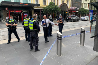 Police inspect broken glass and a damaged bollard in Bourke Street Mall, where a driver has caused chaos, causing pedestrians to jump out of the way, according to witnesses.