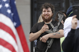 Kevin King cradles an assault rifle as he stands on the top of the Capitol steps at a protest opposing Washington state's stay-home order to slow the coronavirus outbreak on Sunday, in Olympia.
