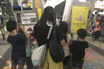 A family write messages on Lennon Wall on a pedestrian bridge above Harcourt Road, before police clear the road with a water cannon.