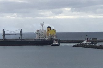 The tugs push and pull at the Panama-registered carrier, carrying 45,000 tonnes of wheat bound for Singapore.
