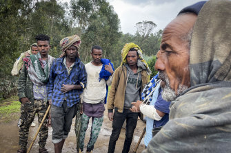 Men gather to speak to injured militia fighter Kibret Bidere, second from right with bandaged arm, after he joined locals to try to fend off Tigrayan soldiers.