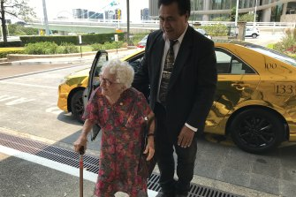 Ipswich's 107-year-old golden girl Liz Jordan, who arrived in a gold cab at the special Christmas lunch for Queensland's 100 Club members at Parliament House, with cab driver Napalu Mate.