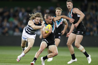 Travis Boak is chased by Tom Guthrie on Thursday night.