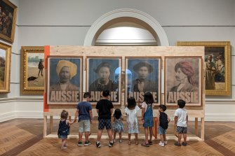 Visitors to the Art Gallery of New South Wales look at Peter Drew's Aussie posters.
