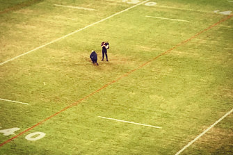 Roosters official Chris James inspects the Bankwest surface long after Friday night's win.