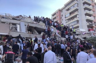 Rescue workers and residents try to rescue people trapped in a collapsed building in Izmir, Turkey, immediately after the earthquake struck.