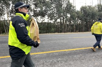 Police take evidence bags from the scene of a search at Mount Hotham on Wednesday.
