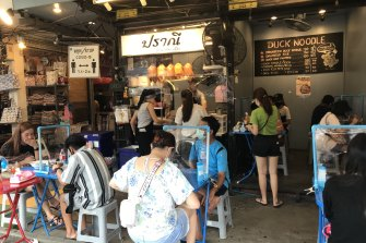 At an eatery at the Chatuchak Weekend Market in Bangkok, partitioned tables and social distancing signs separate a few local customers. Foreigners, the market's main visitors, are still not allowed in the country.