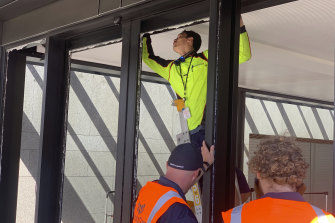 Workers inspect the smashed front doors of the New Zealand Parliament on Wednesday.