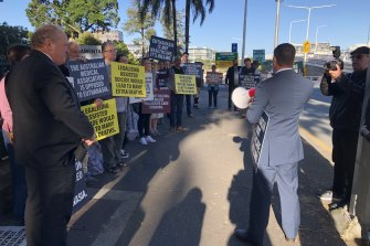 Katter's Australian Party MP Nick Dametto speaks to protesters outside the Queensland Parliament, while fellow KAP member Shane Knuth watches on.