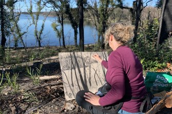 Penny Lovelock sketches with charcoal in the ruins of Lake Conjola.