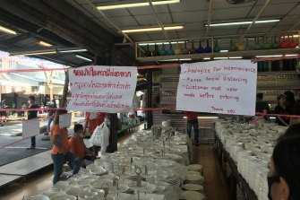 Signs remind visitors to maintain social distancing at the Chatuchak Weekend Market.