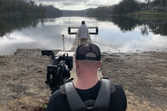 Brennan (in front) films poet Stephen Chinnock on Lake Conjola, making his film We are Conjola.